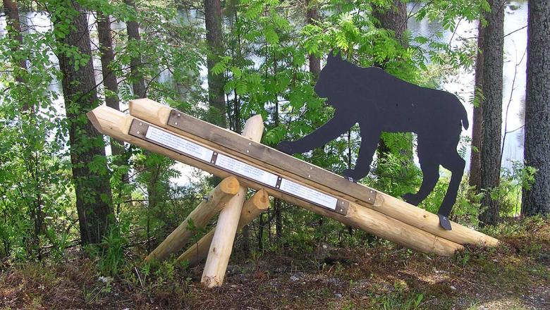 Metallinen aidon ilveksen kokoinen ilvespatsas puisella jalustalla metsän reunassa. Taustalla järvi.