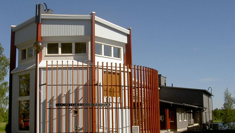 En hög och kantig byggnad med en skylt på väggen där det står naturum Petola.